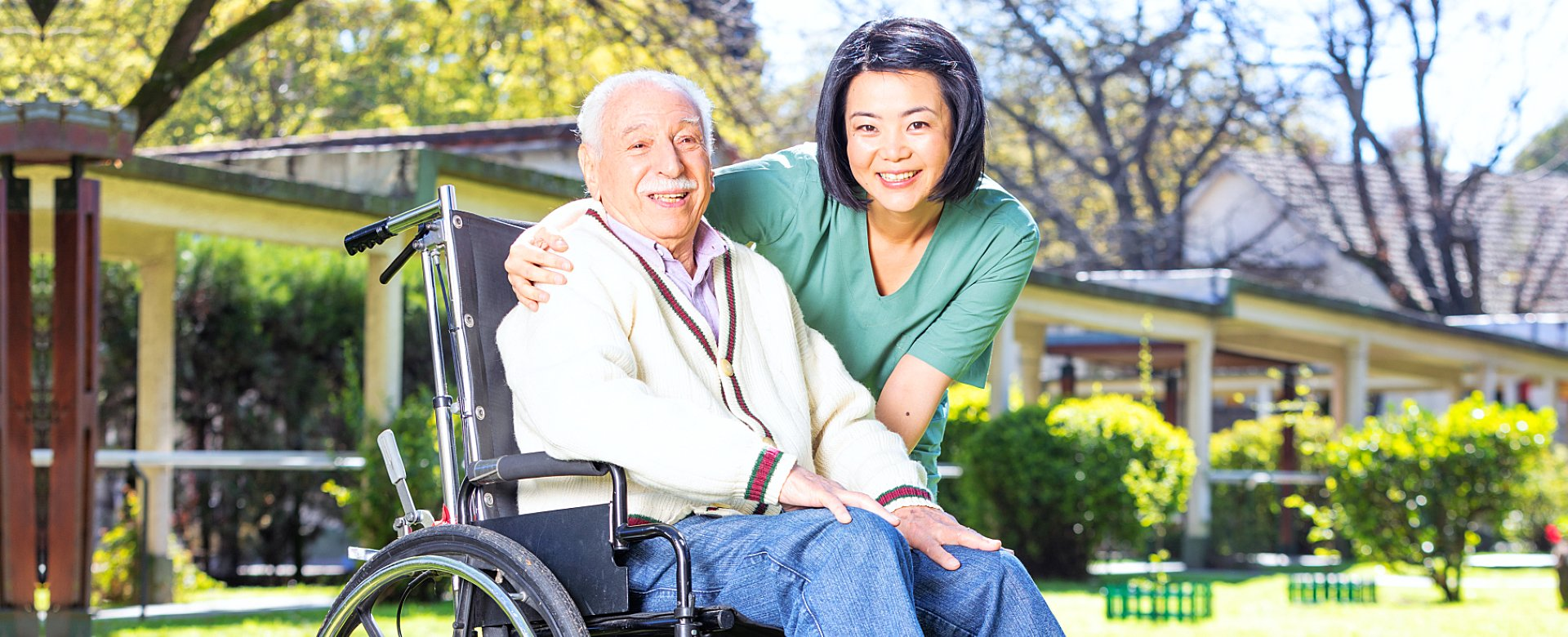 caregiver and elder man in a wheelchair smiling