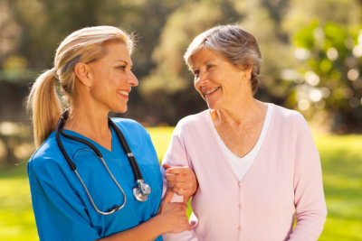 Caring nurse talking to senior women outdoors